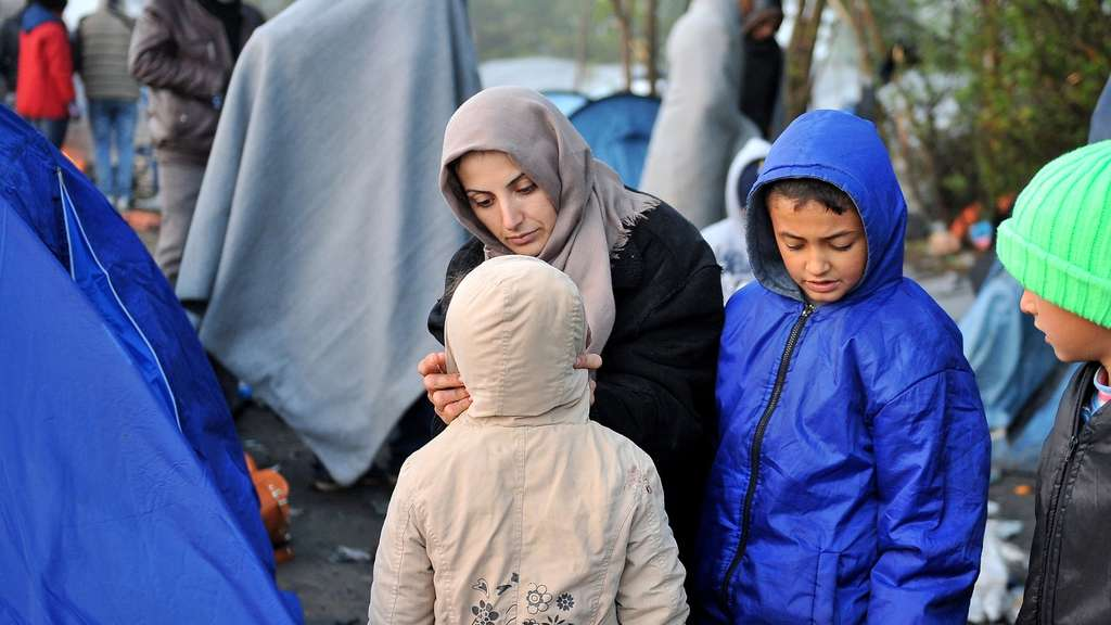 A man carries his child as he walks with other migrants and refugees to cross the Serbian-Croatian border in the village of Berkasovo, near the North-Western Serbian town of Sid, on October 24, 2015 . The prime ministers of Serbia, Bulgaria and Romania were to hold talks on how to tackle record numbers of migrants at the onset of winter, ahead of a mini-EU summit to discuss a coordinated response. Serbia, Bulgaria and Romania are among the countries on the migrants&#39 route from Turkey up through the Balkans to northern Europe. AFP PHOTO / ELVIS BARUKCIC