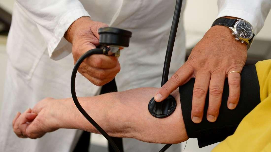 Arzt misst Blutdruck bei einem Patienten