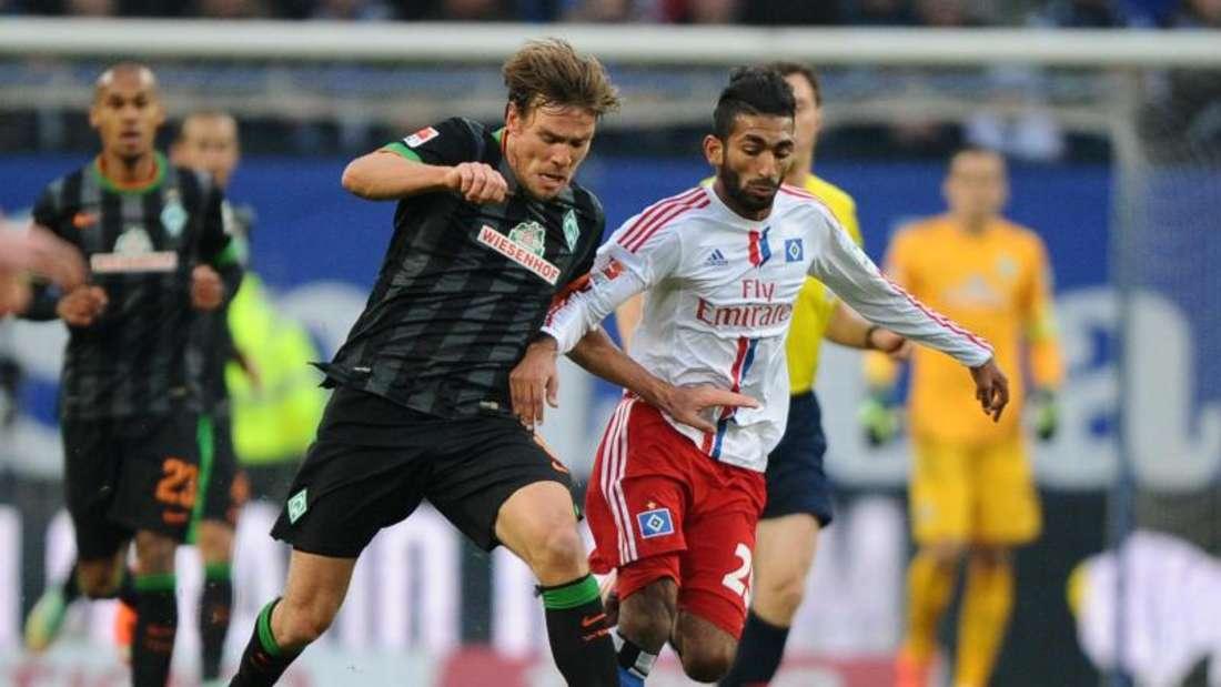 Clemens Fritz (l) steckt nach der Niederlage beim HSV mit Bremen in einer bedrohlichen Lage. Foto: Daniel Bockwoldt