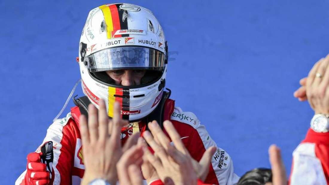 Sebastian Vettel feiert mit der Ferrari-Crew den dritten Platz. Foto: Srdjan Suki