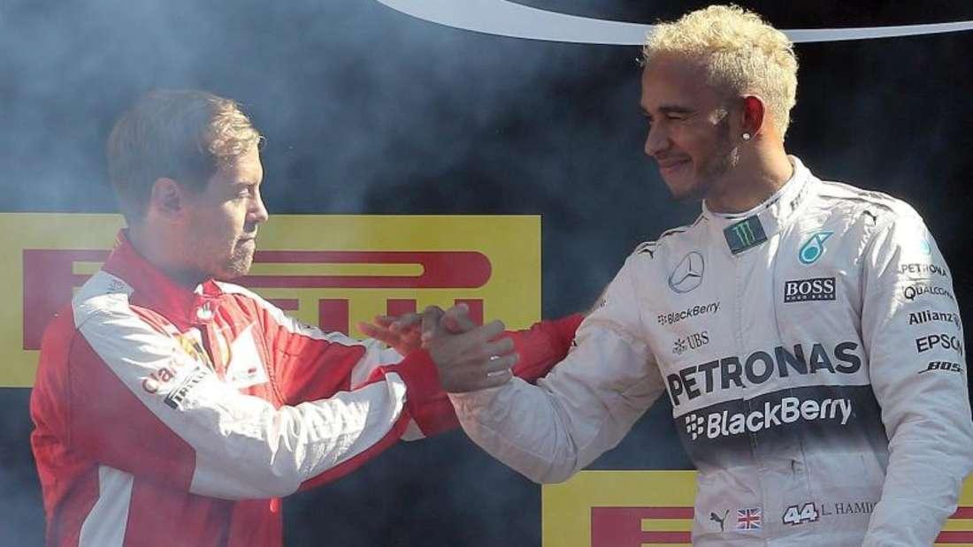 Sebastian Vettel gratuliert den erblondeten Lewis Hamilton zum Sieg. Foto: Daniel Dal Zennaro