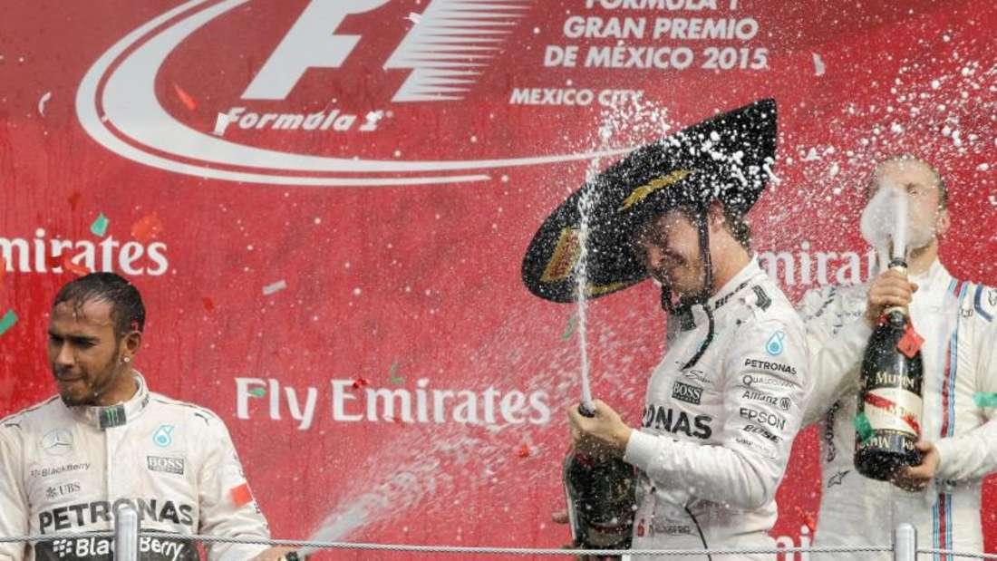 Nico Rosberg (M) feiert auf dem Podest mit Lewis Hamilton (l) und Valtteri Bottas mit Schaumwein. Foto: Ulises Ruiz Basurto