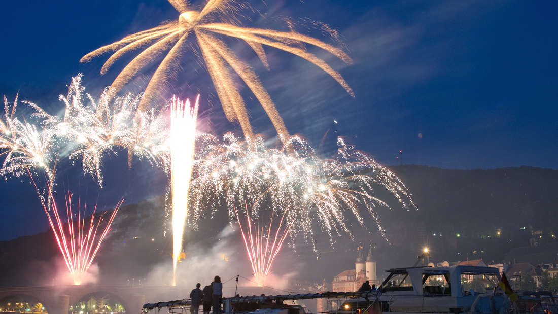 Auf Booten im Neckar betrachten Zuschauer am Samstagabend (04.06.2011) in Heidelberg das Feuerwerk zum diesjährigen Auftakt der Heidelberger Schlossbeleuchtung. Drei Mal im Jahr wird die Schlossruine in rotes Licht gehüllt, in Erinnerung an die Zerstö†rung des Schlosses im pfälzischen Erbfolgekrieg. Anschließ'end wird ein rund 20-minütiges Feuerwerk präsentiert. Foto: Uwe Anspach dpa/lsw +++(c) dpa - Bildfunk+++