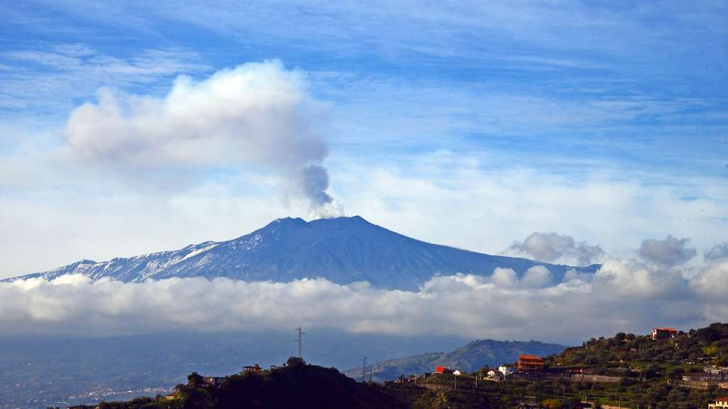 Smoke rises over the city of Taormina during an eruption of the Mount Etna, one of the most active volcanoes in the world, near Catania, on December 4, 2015. / AFP / GIOVANNI ISOLINO