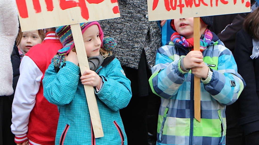 Beim stillen Protest gegen die Verkehrspolitik vorm Rathaus sind auch viele Kinder dabei.
