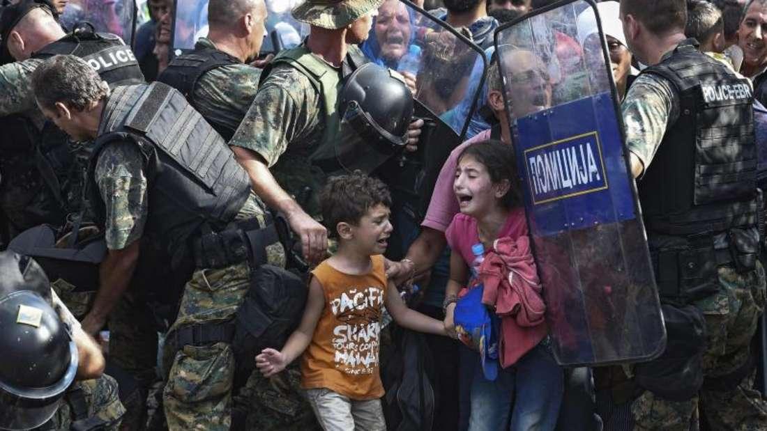 Zwei Kinder auf der griechisch Seite der Grenze zu Mazdonien. Ihre Mutter wird von den Schildern der Polizisten abgedrängt. Foto: Georgi Licovski/Archiv
