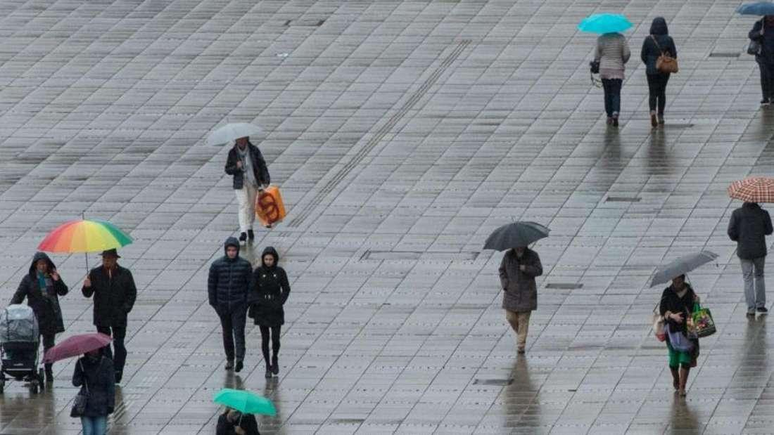 Wohl dem, der an einen Regenschirm gedacht hat: Fußgänger auf dem Stuttgarter Schlossplatz. Foto: Marijan Murat