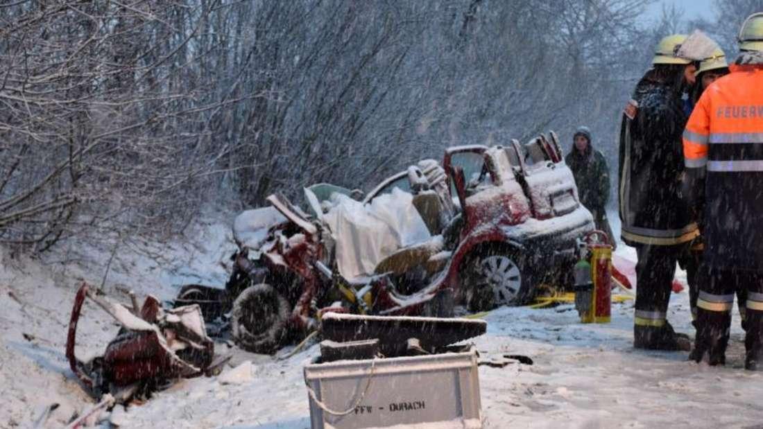 Einsatzkräfte neben einem Fahrzeugwrack im bayerischen Bodelsberg: Bei einem Unfall auf schneeglatter Straße ist eine Autoinsassin ums Leben gekommen. Foto: Benjamin Liss