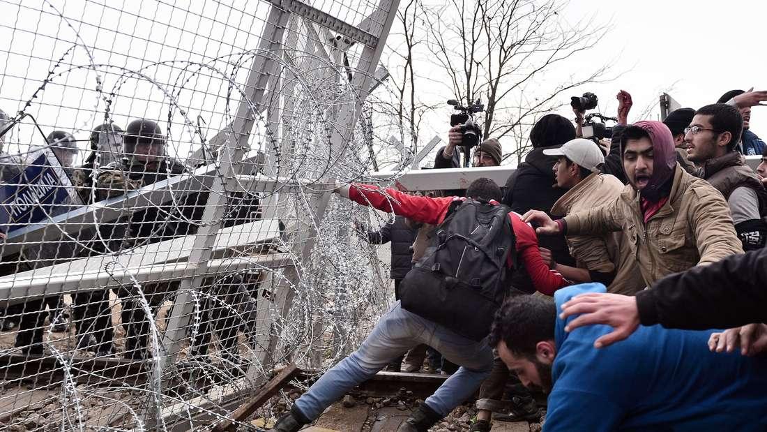 Migranten versuchen an der griechisch-mazedonischen Grenze in Idomeni einen Zaun einzureißen.