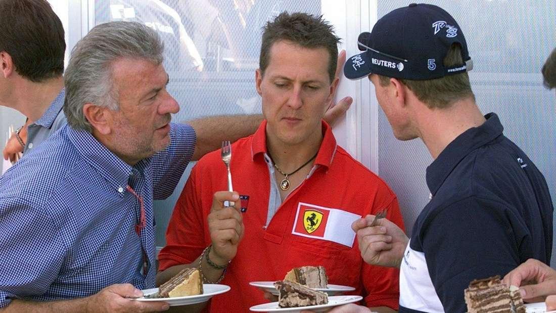 Michael Schumacher (Mitte) im Gespräch mit Bruder Ralf (r.) und ihr Manager Willi Weber in Magny-Cours (Foto vom 30.06.2001).
