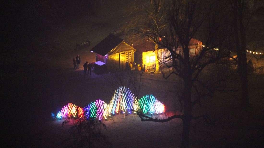Die mit 20 Scheinwerfern beleuchtete 'Welle' (25x4 Meter) aus Holzlatten an der Brunnenlandschaft.