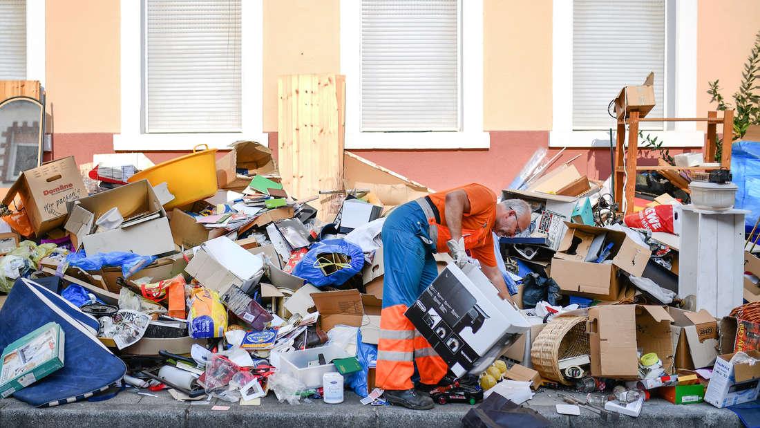 Ein Mitarbeiter der Müllabfuhr entsorgt illegal abgelegten Sperrmüll in Mannheim.