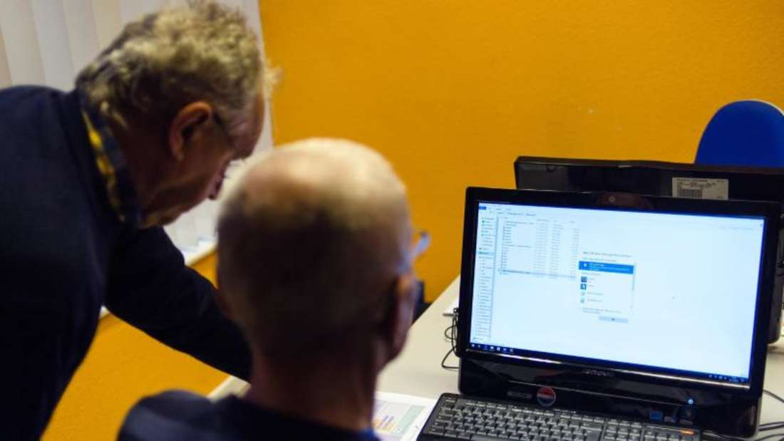 Die beiden Senioren Manfred (l.) und Klaus-Dieter (r.) besprechen beim Computerkurs des SeniorenComputerClubs in Berlin-Mitte ein PC-Problem. Foto: Sebastian Gollnow