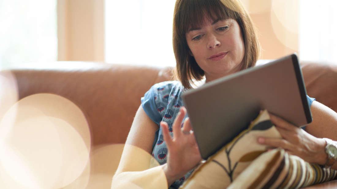 Über das Tablet das Licht im Wohnzimmer einstellen: Smarte Beleuchtungssysteme übernehmen heute das Lichtmanagement - und heben Ihre Stimmung.