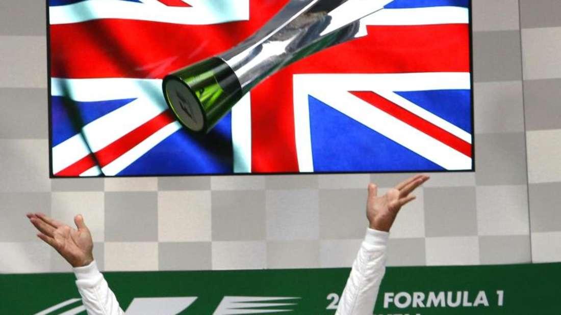 Shanghai-Sieger Lewis Hamilton wirft seine Trophäe in die Luft. Foto: Toru Takahashi