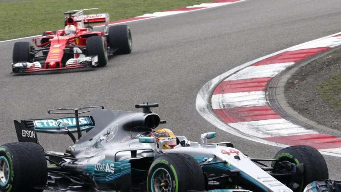 Mercedes-Pilot Lewis Hamilton (r) führt in Shanghai vor Ferrari-Fahrer Sebastian Vettel. Foto: Toru Takahashi
