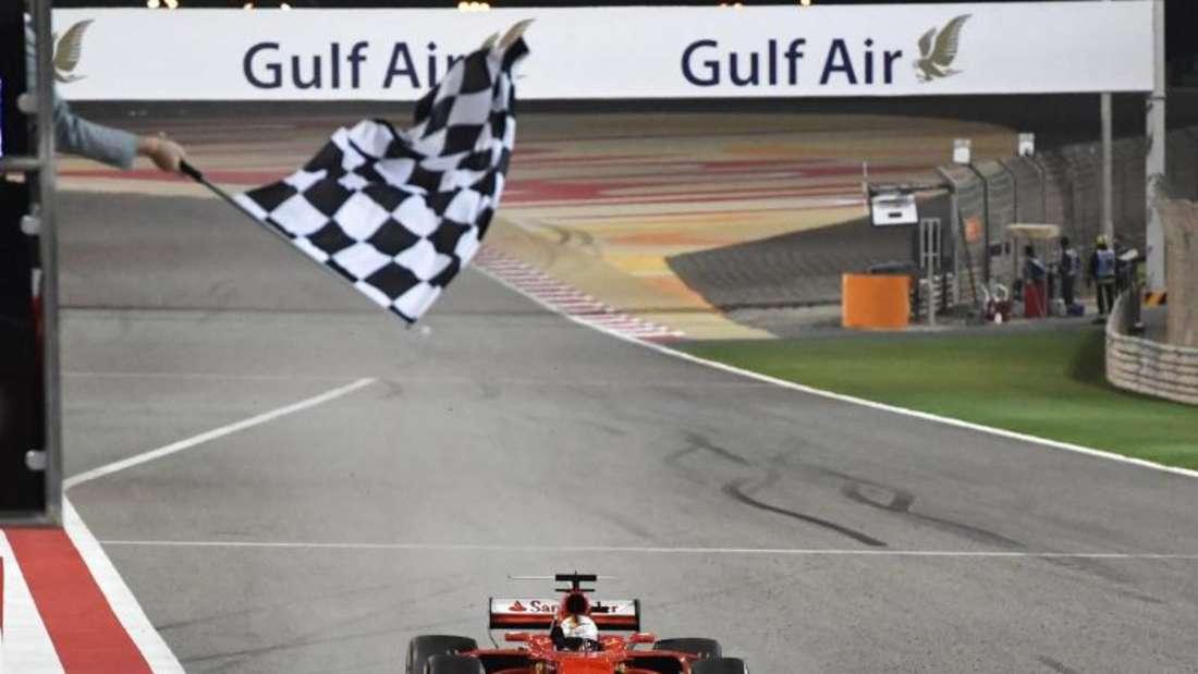 Sebastian Vettel rast mit seinem Ferrari als Erster in Bahrain über die Ziellinie. Foto:Andrej Isakovic
