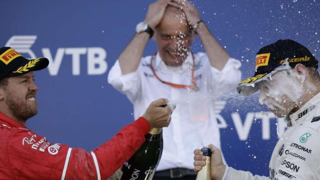 Sebastian Vettel (l) gratulierte dem Sieger auf dem Podium auf seine Weise. Foto: Pavel Golovkin