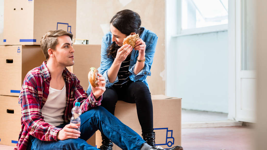 Young couple looking tired while eating a sandwich during break