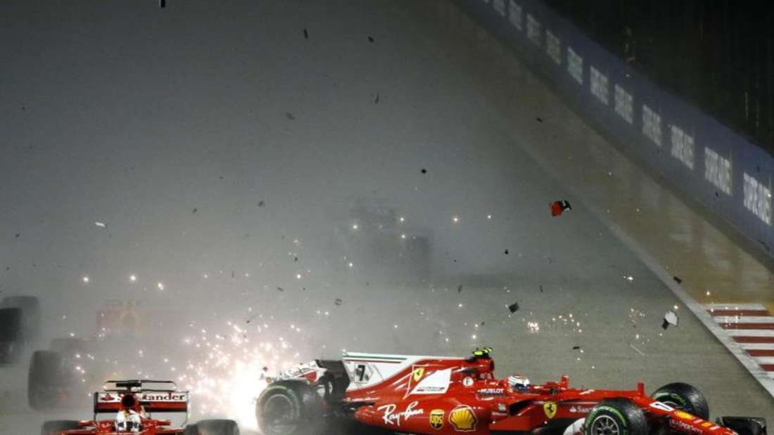 Ferrari-Pilot Kimi Räikkönen (r) kollidiert am Start mit seinem Team-Kollegen Sebastian Vettel. Foto: Yong Teck Lim