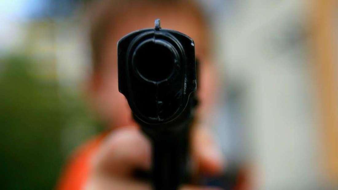 Mann zielt mit Schusswaffe