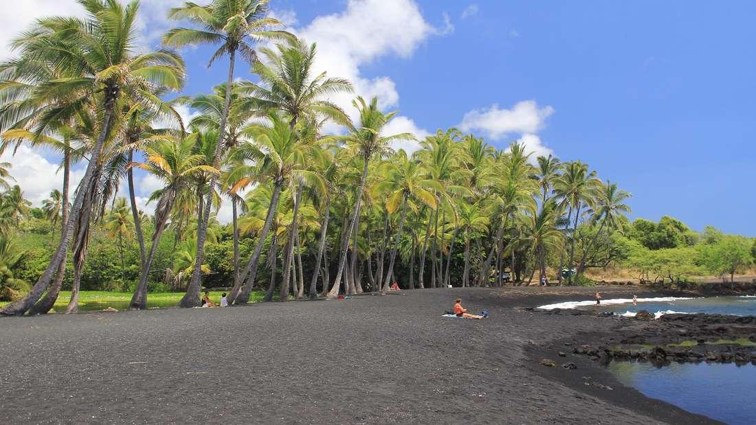 Punaluu Black Sand Beach, Hawaii, USA: Hawaii ist die Insel der Vulkane – daher finden sich dort besonders viele schwarze Sandstrände. Der Punaluu Black Sand Beach ist nicht nur mit Palmen gesäumt, auch finden hier zahlreiche hawaiianische grüne Seeschildkröten ihre Heimat, die dort unter Artenschutz stehen.