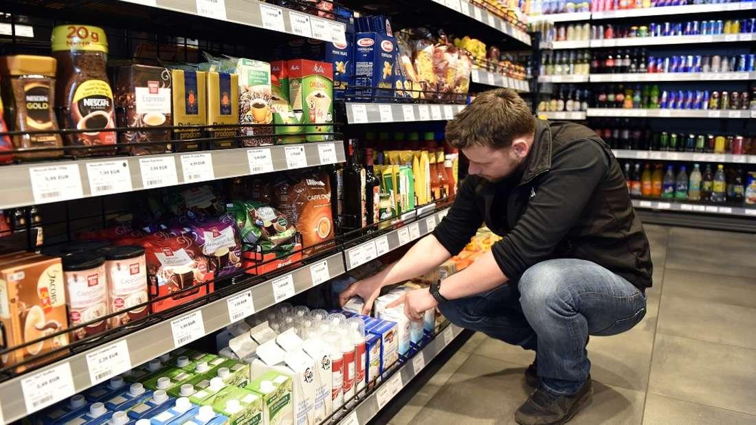 Ein Mitarbeiter sortiert Regale im Supermarkt ein. Doch wie viel verdient man im Einzelhandel?