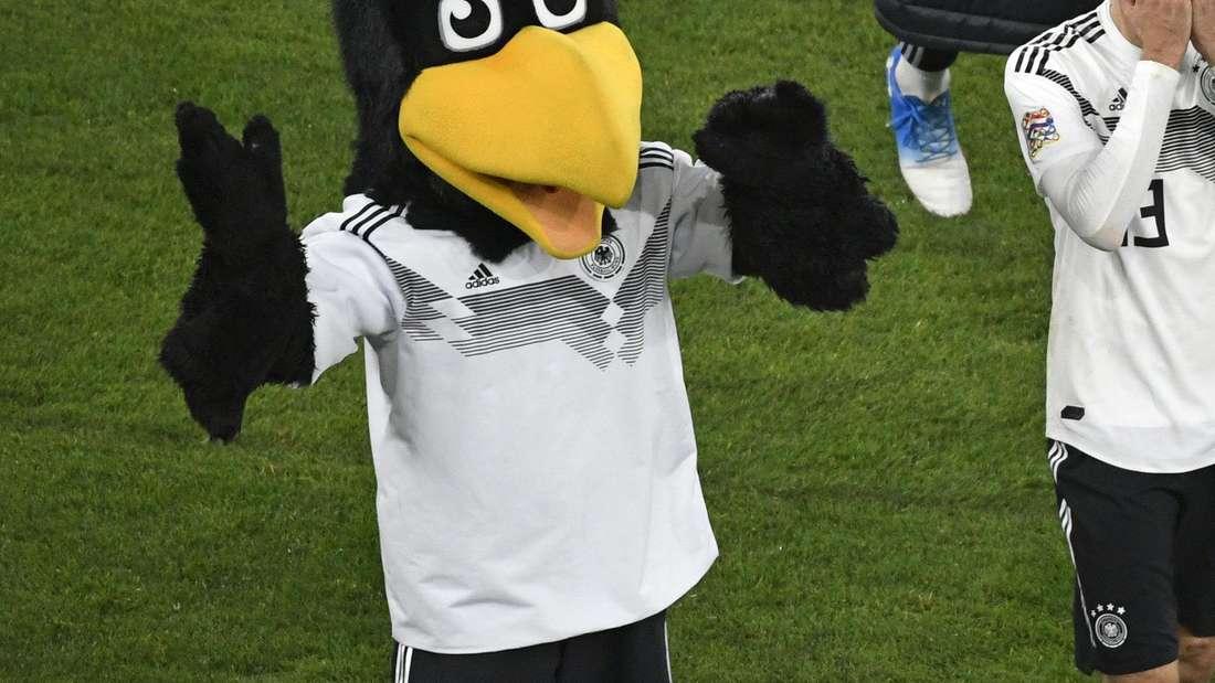 Thomas Müller geht nach dem Spiel neben Maskottchen Paule enttäuscht über den Platz.
