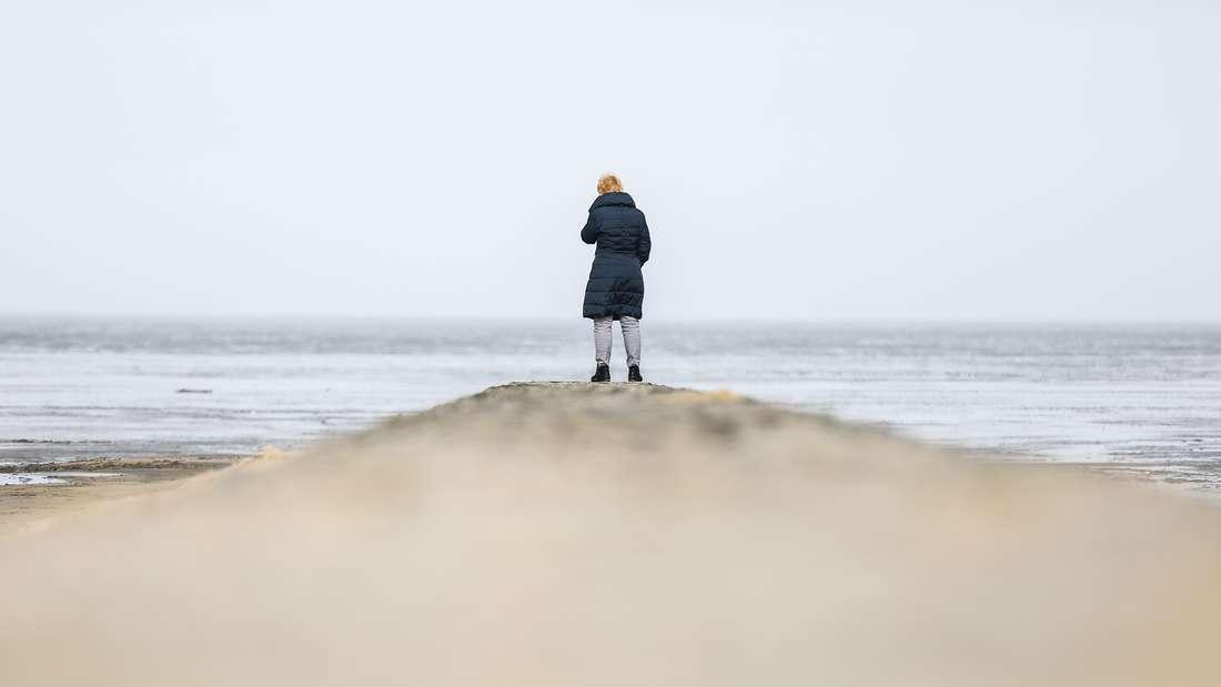DasBild einer Frau am Strand wird durch ein übernatürliches Detail gestört - erkennen Sie es? (Symbolbild)
