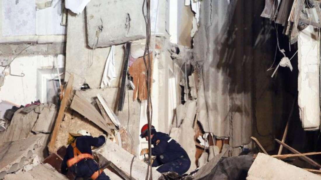 Rettungskräfte arbeiten in dem eingestürzten Mehrfamilienhaus. Foto: Maxim Shmakov/AP