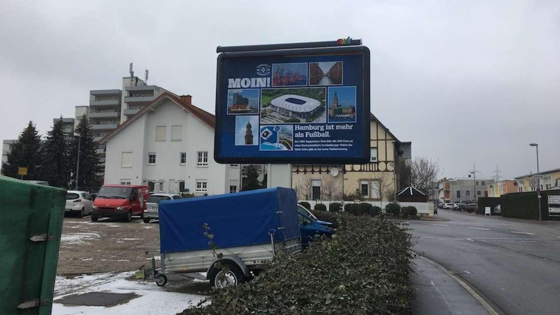 Am Sandhäuser Bahnhof ist ein riesiges Plakat des Hamburger SV zu sehen.