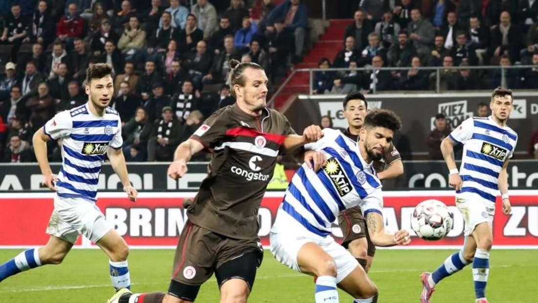 St. Paulis Alex Meyer (l) kann sich nicht gegen den Duisburger Enis Hajri im Zweikampf durchsetzen. Foto: Chrisitan Charisius/dpa