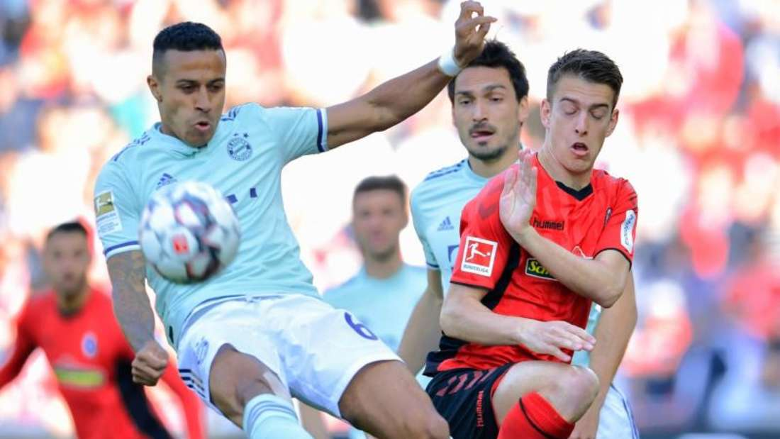 Münchens Thiago (l) und Freiburgs Janik Haberer im Zweikampf um den Ball. Foto: Uwe Anspach/dpa