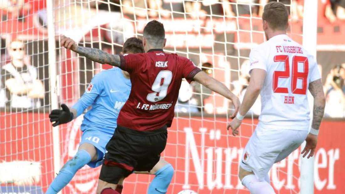 Der Nürnberger Mikael Ishak (M) erzielt trotz der Augsburger Gregor Kobel (l) und Andre Hahn den Treffer zum 1:0. Foto: Daniel Karmann/dpa