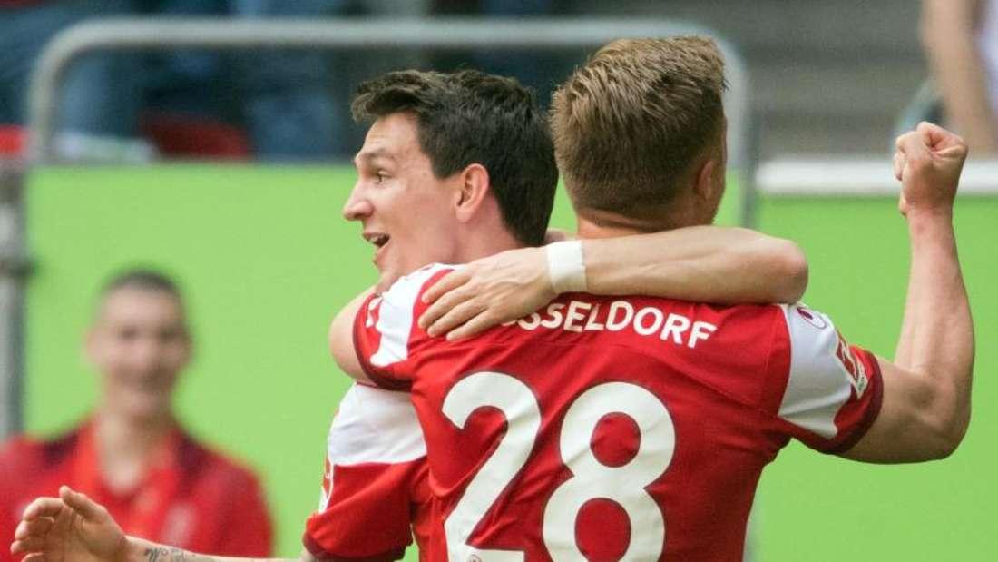 Die Düsseldorfer Rouwen Hennings (r) und Benito Raman feiern das Tor zum 3:0. Foto: Federico Gambarini/dpa