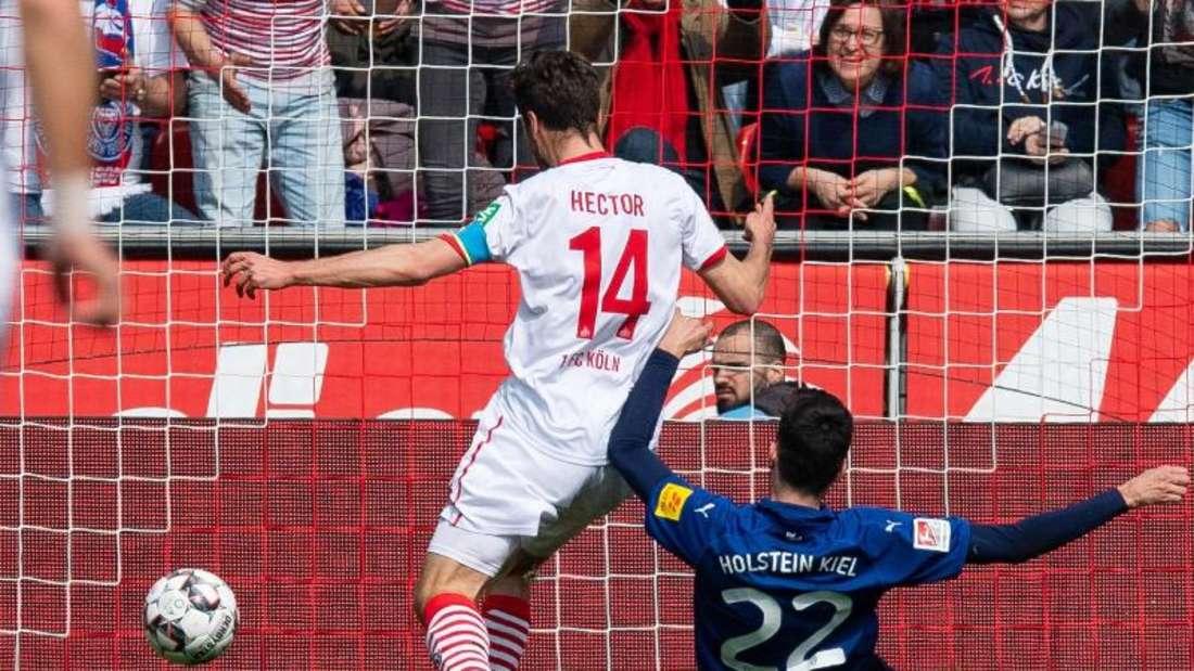 Kölns Jonas Hector (l) erzielt gegen Kiels Atakan Karazor das Tor zum 2:0. Foto: Guido Kirchner