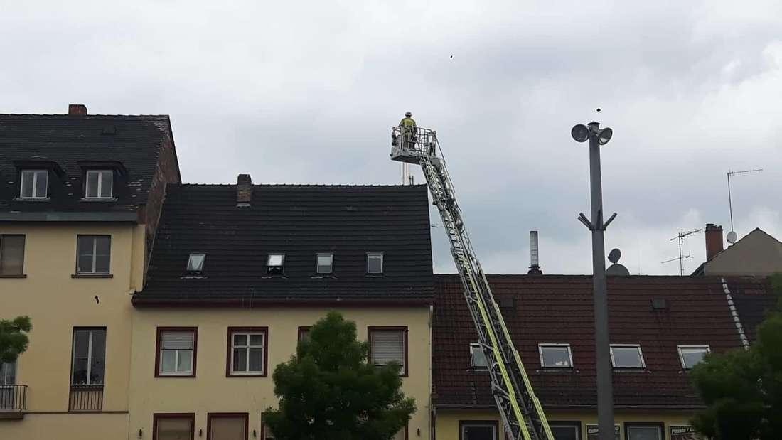 Mit einer Drehleiter löscht ein Feuerwehrmann den Kamin.