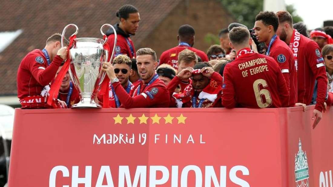 Liverpools Spieler fahren in einem offenen Bus durch die Stadt und lassen sich feiern. Foto: Barrington Coombs/PA Wire