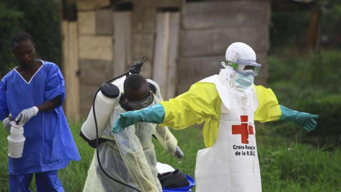 Helfer reinigen sich nach der Arbeit in einem Behandlungszentrum gegen Ebola mit Desinfektionsmittel. Im Kongo sind inzwischen mehr als 2000 Menschen an dem gefährlichen Ebola-Virus erkrankt. Foto: Al-Hadji Kudra Maliro/AP