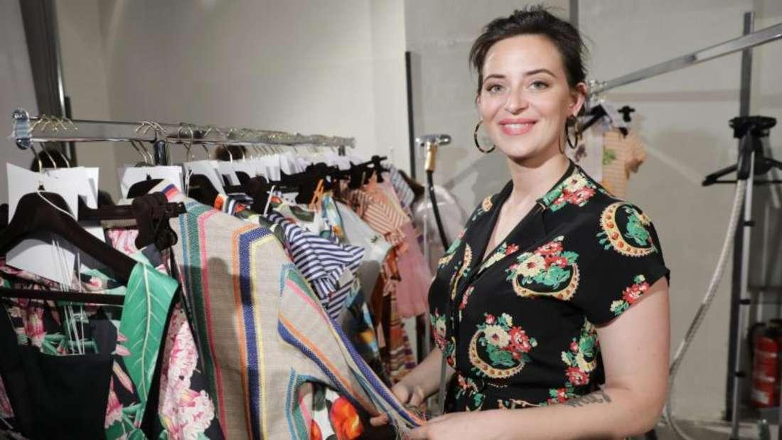 Designerin Lena Hoschek neben ihren Kleidern auf der Fashion Week 2018. Foto: Jörg Carstensen