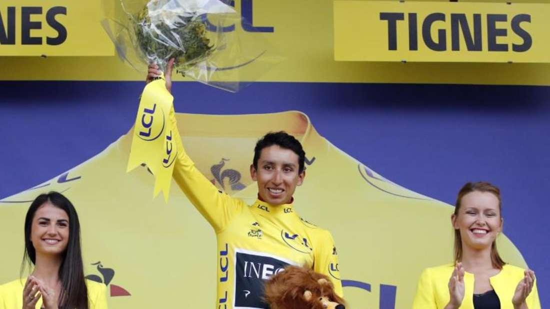 Egan Arley Bernal Gomez (M) steht im Gelben Trikot des Gesamtführenden auf dem Podium. Foto: Christophe Ena/AP