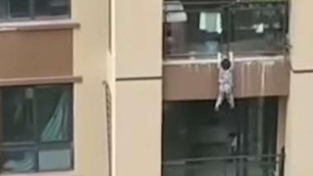 Verzweifelt versucht der Dreijährige in China wieder auf den Balkon zu kommen.