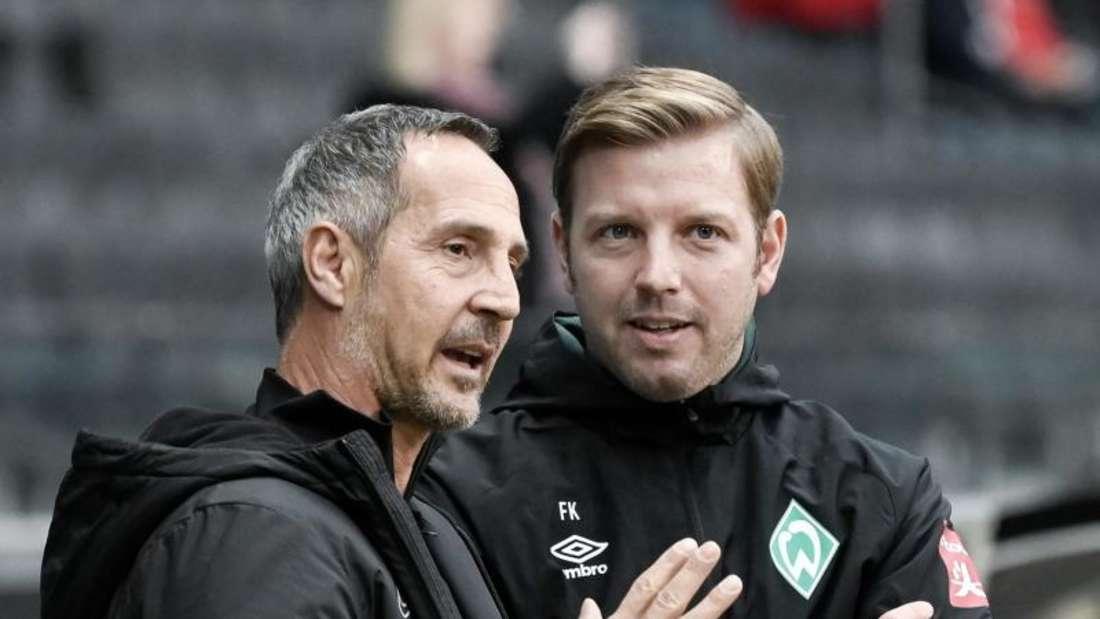 Frankfurts Trainer Adi Hütter (l) und sein Bremer Kollege Florian Kohfeldt (r) unterhalten sich vor Spielbeginn. Foto: Silas Stein/dpa