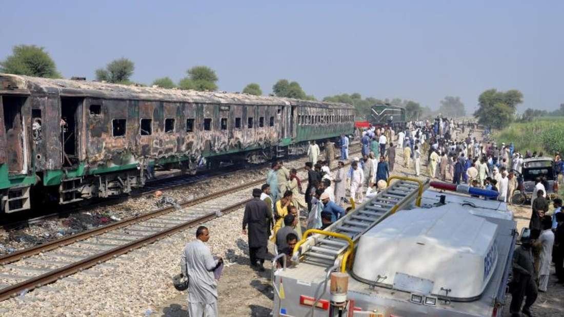 Ein Rettungswagen steht neben dem ausgebrannten Personenzug. Foto: Siddique Baluch/AP/dpa