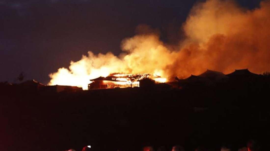 Menschen beobachten den Brand der historischen Shuri Burg. Foto: Jun Hirata/Kyodo News/AP/dpa