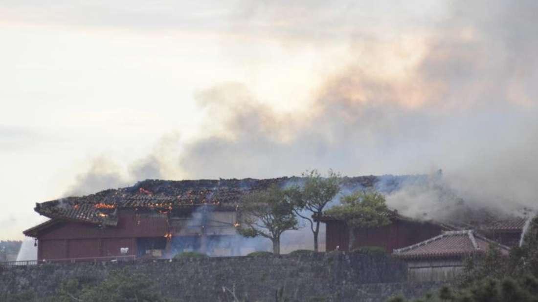 Das Hauptgebäude der Burg qualmt nach dem Brand. Foto: -/kyodo/dpa