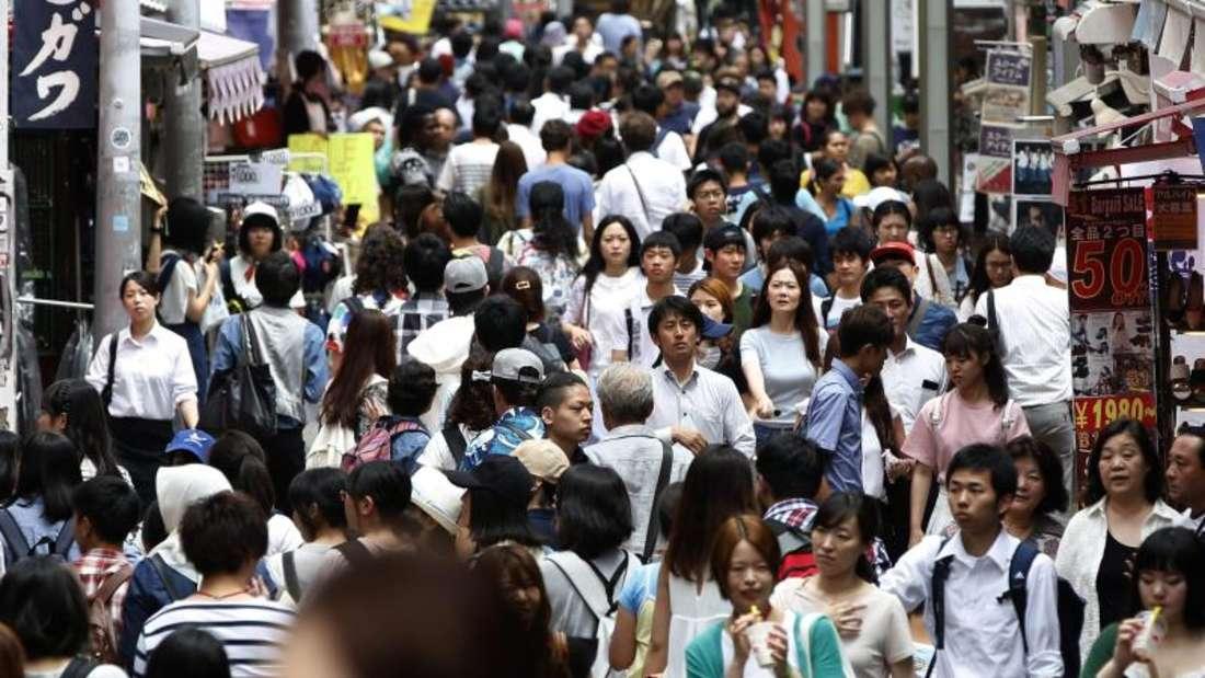 Menschen drängen sich auf einer Straße der Stadt. Foto: Yuya Shino/epa/dpa