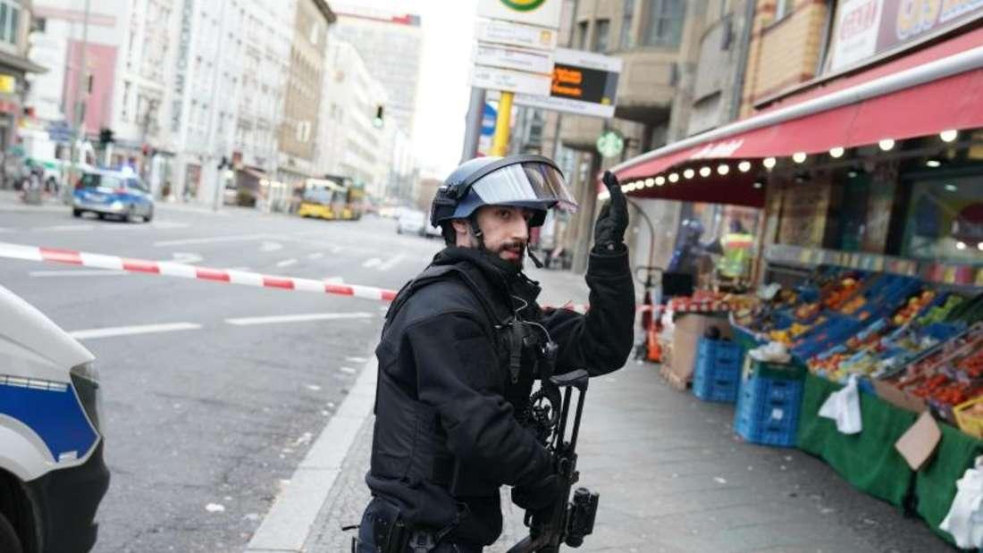 Ein Polizist in Schutzausrüstung weist Passanten an, sich in Sicherheit zu bringen. Foto: Kay Nietfeld/dpa