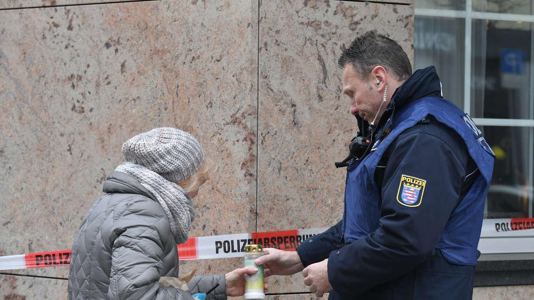 Ein Polizist hilft einer Frau in der Nähe des Tatortes am Heumarkt eine Kerze anzuzünden.