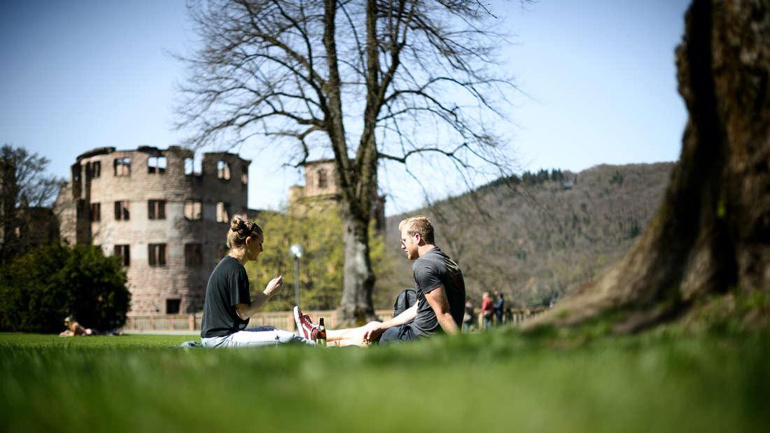 Ein Pärchen sitzt in der Sonne vor dem Heidelberger Schloss (Archivfoto).